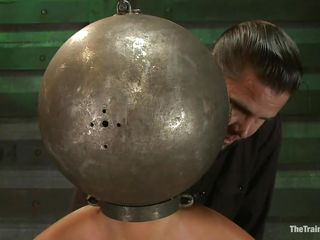 Adrianna Luna has her legs held apart by a support and her hands are encased by metal balls. Her head is encased by a metal ball as well and pumps on her nipples. She gets a vibrator on her pussy and gets the ok to cum. Then she's tied to a table and having clamps put on her pussy and tits. Freaky!