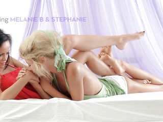 Horny harlots Stephanie and Melanie are sitting very close on white sheets. They are cuddling and begin giving a kiss each other. The sluts take their clothes off one by one and reveal sexy white panties. As playful as a kitten, Melanie presses her hard nipps to Stephanie`s carnal back. Wanna peek?