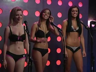 The Playboy Morning Show this time has three nice-looking angels in their bras and pants on a stage. The special guest is Mindy Sterling, a veteran actress most famous for playing Frau Farbissina in the Austin Powers movies. She's teaching the angels a bit on doing improv comedy with ideas from callers.