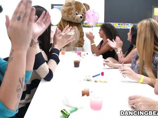 A stripper in a bear suit has arrived for a bachelorette party. The women caress his groin to lure his cock out. They get him out of his suit to see his rod. They suck him off with glee whilst having a party.