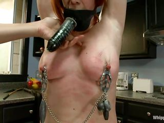 Odille has a strap on fake penis attached on her face and with her hands tied and clamps on her nipples and pussy she waits patiently in the kitchen for the golden-haired milf to undress. After the golden-haired is naked, with a little help and guidance she insets the fake penis in that shaved cunt, fucking it like a submissive slut.
