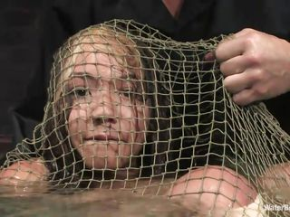 Keeani Lei has her hands fastened behind her back and she's balled up in a large net bag. Suspended over the water tank, that babe gets an abrupt release, dunking her into the water. That babe gets dunked and held under several times. That babe looks sexy all undressed and helpless in that net, but that babe looks scared to death!