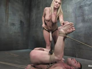 The dominating golden-haired milf wishes the man's penis but that babe wishes to fuck his ass even more! After tieing him with his legs up that babe sucks his penis and plays with his tight shaved asshole previous to inserting a huge strap on sex-toy in it. He groans as the sex-toy goes deep in his rectum and has to obey in front of the breasty golden-haired