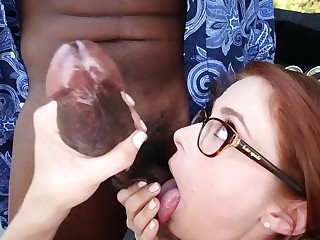 Redhead with glasses is tasting a fat dark lend substance stick. She rides drenching too