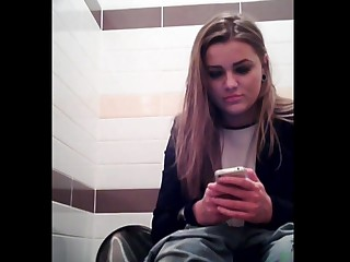 Inferior girl is playing with phone pissing on toilet