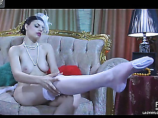 Dressed in vintage style bombshell slowly rolls down her white satin top stockings