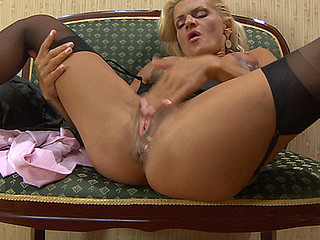 Stacked blonde in glasses parts her stockinged legs to finger fuck her box
