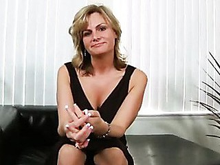 Alluring golden-haired cougar masturbates on a leather bed