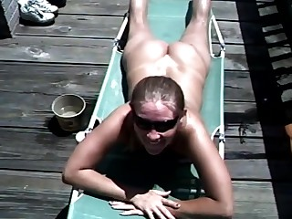 The sexy blonde is sunbathing naked on a the deck near the beach. Her boyfriend approaches. The sexy sun has made the girl's blood boil and she gives him a steamy blowjob. The guy cums in her mouth.