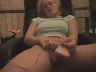 Randy blonde lady with large boobs covered with green t-shirt moves aside her panties to fill wet cunt with very natural looking dildo.