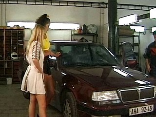 At the garage, two horny ladies go lezzie on each other and later have the mechanic join in