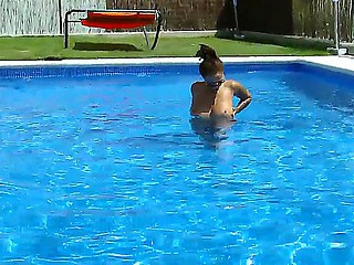 Horny chick Domino enjoys teasing and posing in the pool by shaking and rubing her tits