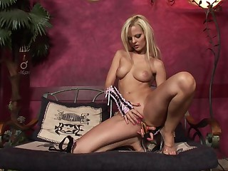 Busty blonde goddess riding a massive golden dildo on the couch