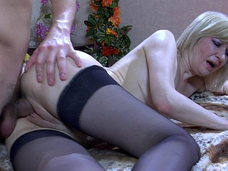Still good-looking golden-haired mamma gets pounded by a youngster on a family settee