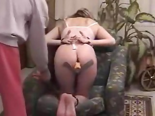 Freaky chick has her hands and feet cuffed and bows over on the sofa helplessly as the dominating dude plugs her pussy. That babe sucks on his penis and that guy ass fucks her with the dildo still in her cunt!